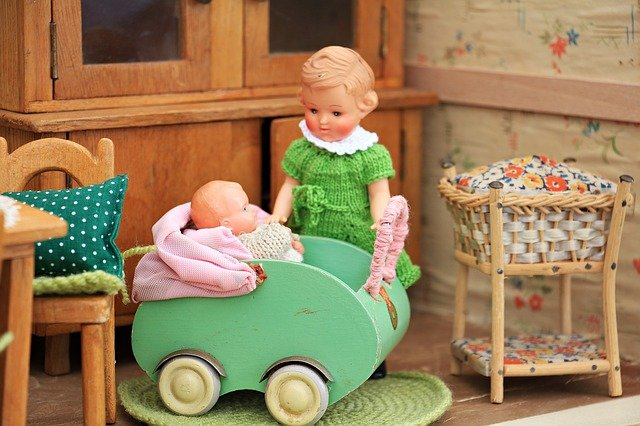 A baby doll sitting in a chair